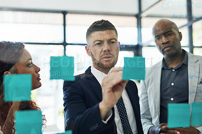 Buy stock photo Shot of a group of businesspeople brainstorming on a glass wall in an office