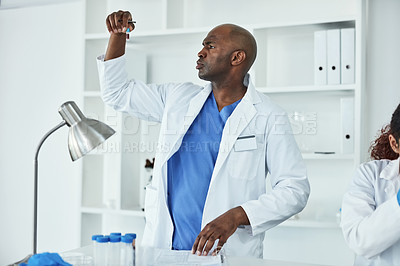 Buy stock photo Shot of a mature scientist analyzing samples in a lab alongside a colleague