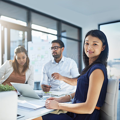 Buy stock photo Portrait of an attractive young businesswomen sitting in her office while her colleagues are having a discussion in the background