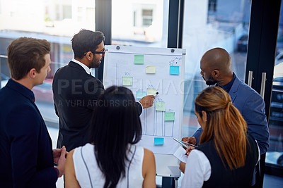 Buy stock photo Shot of a young businessman giving a demonstration on a white board to his colleagues in a modern office