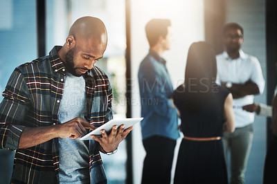 Buy stock photo Shot of a young businessman using his digital tablet in a modern office with his colleagues in the background