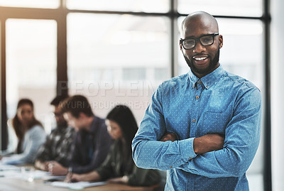 Buy stock photo Portrait of a cheerful businessman posing with his arms folded in a modern office with his colleagues in the background