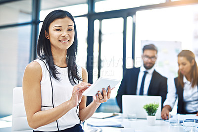 Buy stock photo Cropped portrait of a businesswoman using a digital tablet with her colleagues in the background