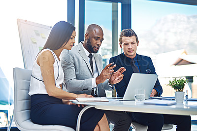 Buy stock photo Cropped shot of a group of businesspeople working together on a laptop in a modern office