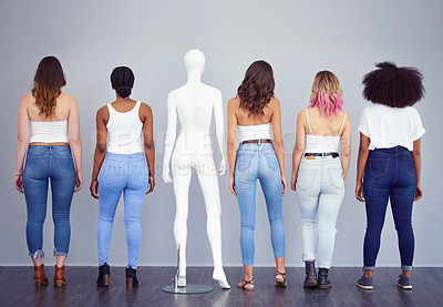 Buy stock photo Rearview studio shot of a group of attractive young women posing with a mannequin against a gray background