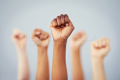 Buy stock photo Cropped studio shot of a group of women raising their fists in solidarity against a gray background