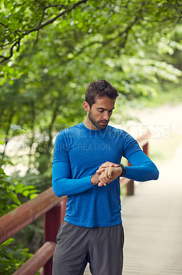 Buy stock photo Shot of a sport middle-aged man looking at the time on his wristwatch while running