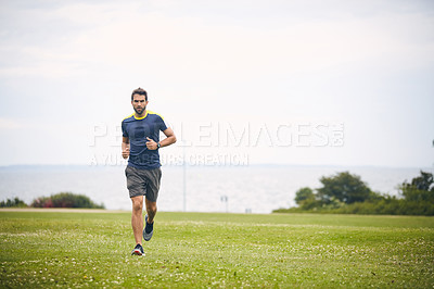 Buy stock photo Shot of a sporty middle-aged man out running in a park