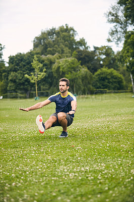 Buy stock photo Shot of a sporty man starting his exercise routine with stretching exercises