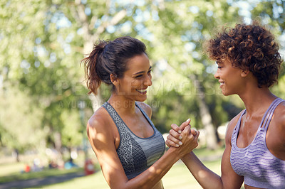 Buy stock photo Cropped shot of two sporty young women exercising outdoors on a sunny day