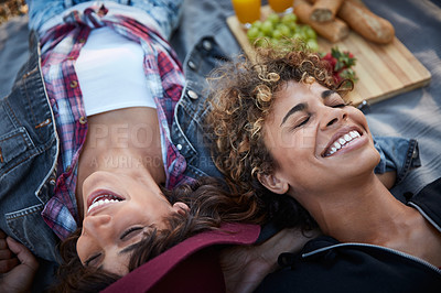 Buy stock photo Cropped shot of two young women lying on a picnic blanket