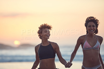Buy stock photo Shot of two young women enjoying themselves at the beach