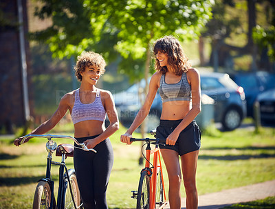 Buy stock photo Shot of two sporty young women out cycling on a sunny day