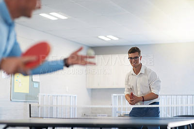 Buy stock photo Shot of two young businessmen playing table tennis at work