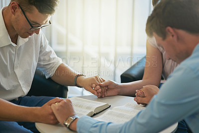 Buy stock photo Shot of a group of young businesspeople holding hands while deep in prayer at work