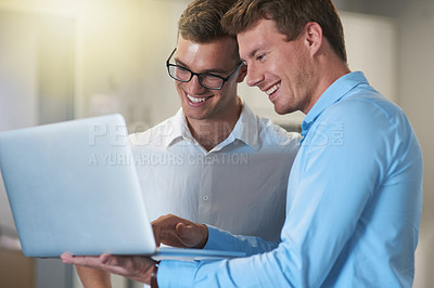 Buy stock photo Shot of two handsome young businessmen working on a laptop together at work