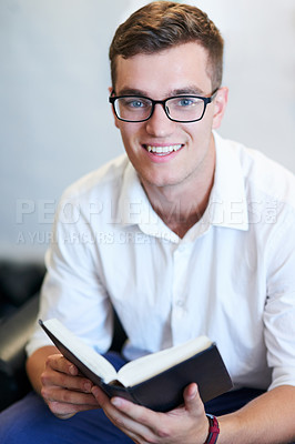 Buy stock photo Portrait of a handsome young businessman reading his bible at work