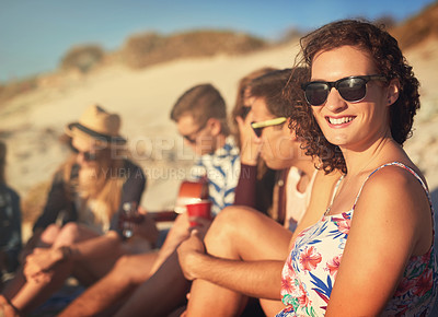 Buy stock photo Cropped portrait of a young woman sitting next to her friends at the beach