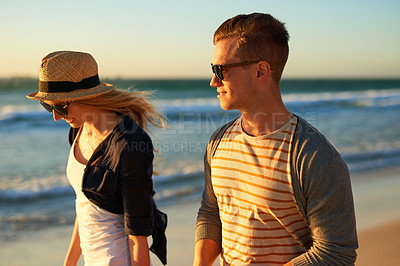 Buy stock photo Cropped shot of n affectionate young couple taking a walk together on the beach