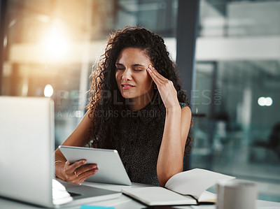 Buy stock photo Shot of a young businesswoman looking stressed out while working late in an office
