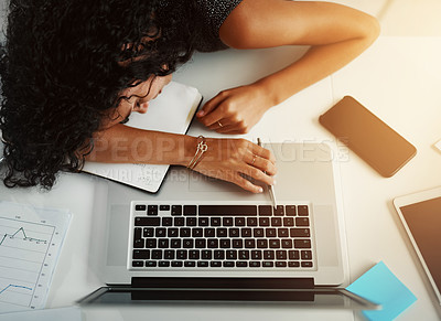 Buy stock photo High angle shot of a young woman sleeping at her desk while working late in an office