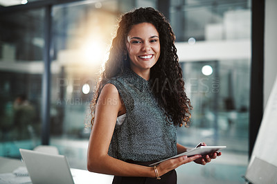 Buy stock photo Portrait of a young businesswoman working on a digital tablet in an office at night