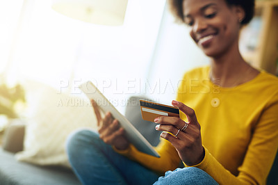 Buy stock photo Cropped shot of a young woman using a digital tablet while relaxing at home
