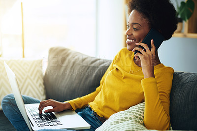 Buy stock photo Shot of a young woman talking on her phone while using her laptop at home