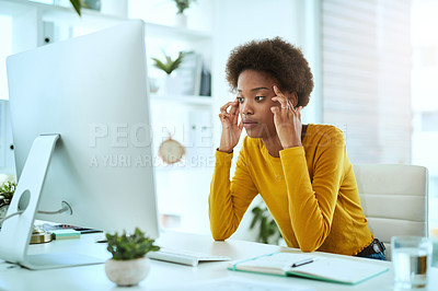 Buy stock photo Shot of a young designer looking stressed out while working in an office