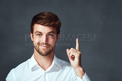 Buy stock photo Studio portrait of a handsome young man pointing to copyspace against a dark background