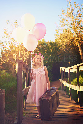 Buy stock photo Shot of a happy little girl holding balloons and a suitcase while standing in the middle of a bridge