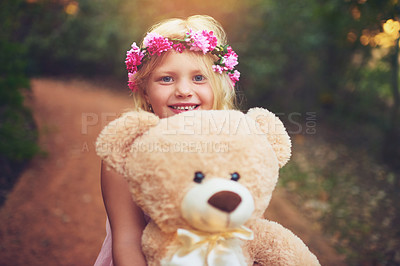 Buy stock photo Shot of a happy little girl holding a teddy bear and looking at the camera while standing in the middle of a dirt road