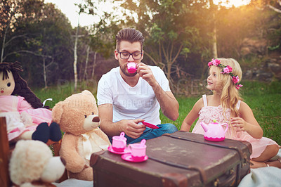 Buy stock photo Shot of a cheerful daughter and father having a tea party with a bunch of stuffed toys in the middle of a garden