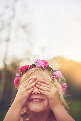 Buy stock photo Shot of a cheerful little girl with her hands on her eyes playing hide and seek outside in nature