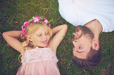 Buy stock photo Shot of a happy daughter and father lying on the ground sticking their tongues out at each other outside in nature