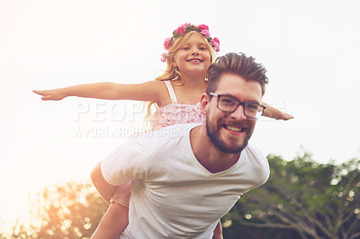 Buy stock photo Shot of a happy father giving his daughter a piggyback ride outside in nature