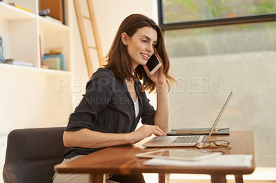 Buy stock photo Shot of a young woman using a smartphone and laptop while working from home