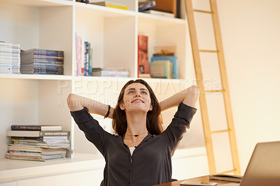 Buy stock photo Shot of a young woman relaxing at her desk while working from home