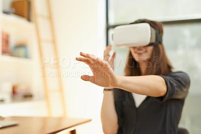 Buy stock photo Shot of a young woman using a virtual reality headset at home