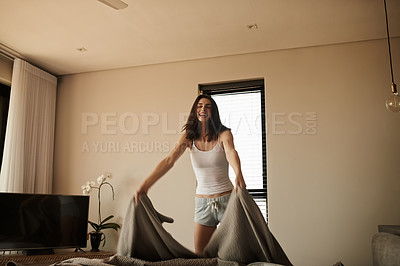 Buy stock photo Shot of a beautiful young woman making the bed in the morning at home