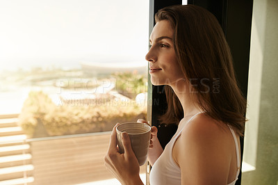 Buy stock photo Shot of a beautiful young woman looking out of the window while having her morning coffee at home