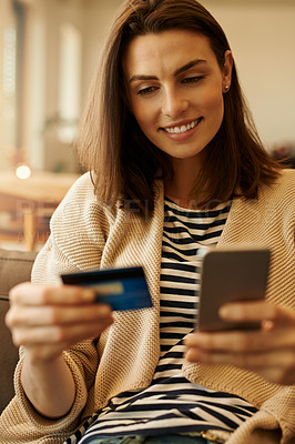 Buy stock photo Shot of a beautiful young woman using a cellphone and credit card at home