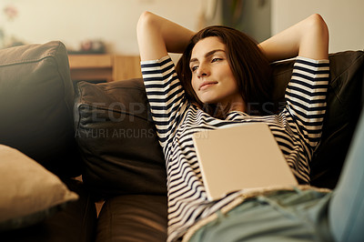 Buy stock photo Shot of a beautiful young woman using a digital tablet at home