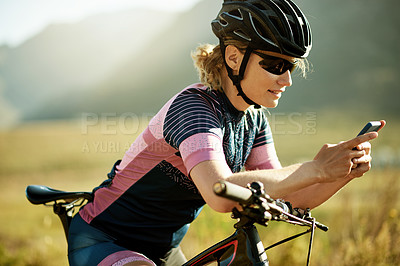 Buy stock photo Shot of a sporty woman using her cellphone while out cycling on a country road