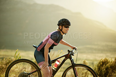 Buy stock photo Shot of a sporty woman experiencing leg pain while out cycling