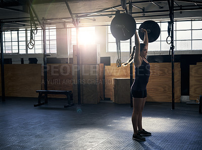 Buy stock photo Full length shot of an attractive young woman working out in the gym