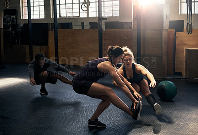 Buy stock photo Full length shot of a group of young athletes working out in the gym