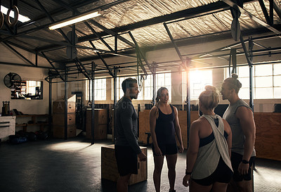 Buy stock photo Cropped shot of a group of young athletes working out in the gym