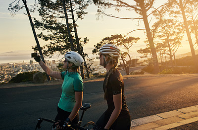 Buy stock photo Cropped shot of two sporty young women taking a selfie while out cycling