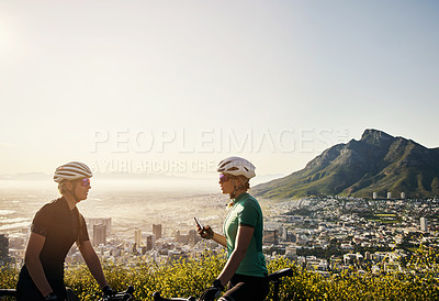 Buy stock photo Shot of two sporty young women chatting while taking a break from cycling